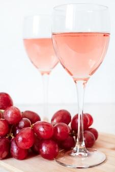 Copos de vinho rosa e uvas vermelhas. duas taças de champanhe.