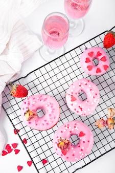 Copos de vinho rosa ou champanhe e rosquinhas rosa na assadeira. conceito de dia dos namorados.