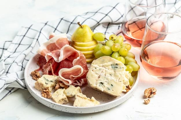 Copos de vinho rosé com pedaço de queijo azul com uvas vibrantes, nozes e pêra, conceito de celebração de festa. fundo de receita de comida. fechar-se.