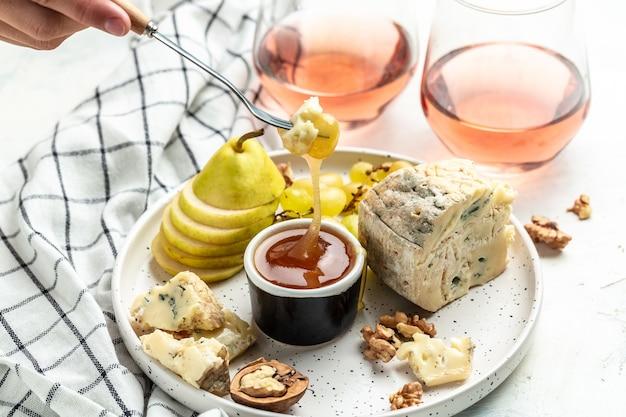 Copos de vinho rosé com pedaço de queijo azul com uvas vibrantes, nozes, mel e pêra, conceito de celebração de festa. fundo de receita de comida. fechar-se.