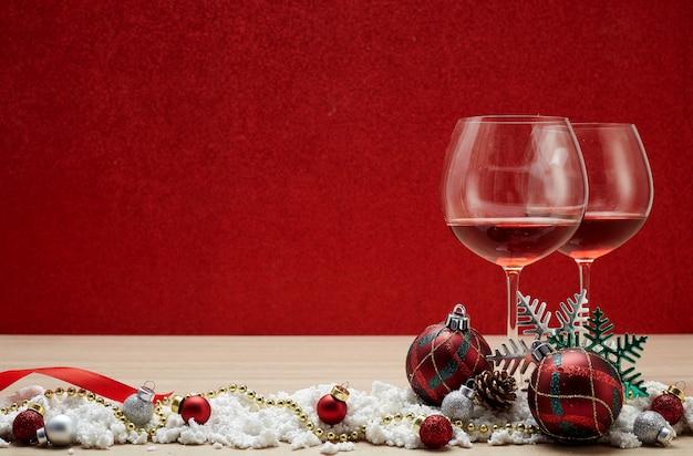 Copos de vinho tinto e bolas de natal na neve