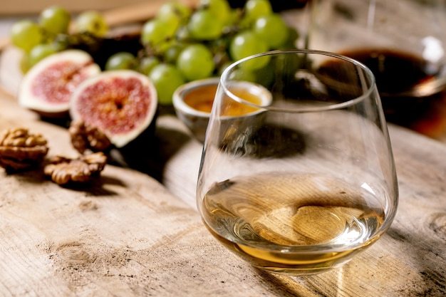 Copos de vinho tinto e branco com uvas, figos, queijo de cabra e nozes sobre a velha mesa de madeira. fechar-se