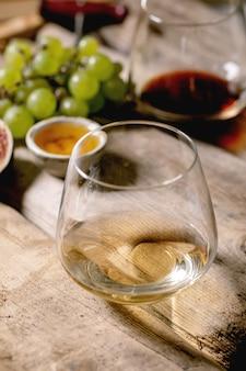 Copos de vinho tinto e branco com uvas, figos, queijo de cabra e nozes sobre velha mesa de madeira