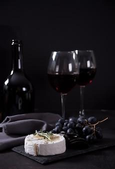 Copos de vinho tinto e prato com diversos queijos, frutas