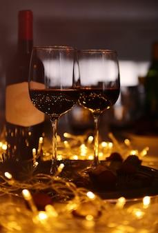 Copos de vinho tinto e trufas de chocolate na mesa decorada closeup