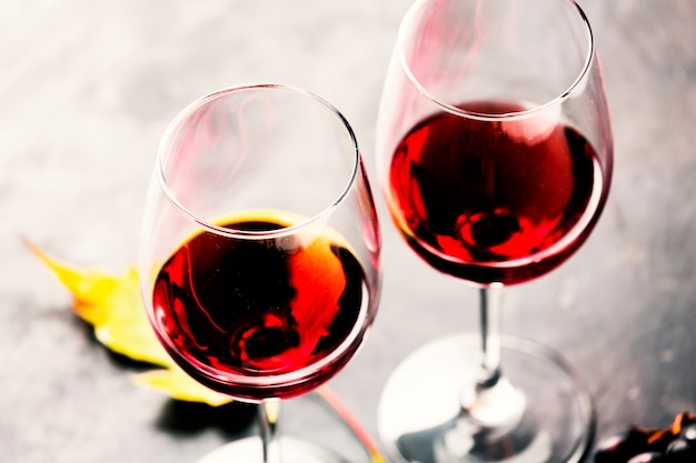 Copos de vinho tinto e uma folha de videira