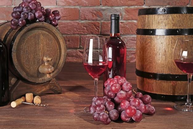 Copos de vinho tinto, uvas e barris de madeira na mesa