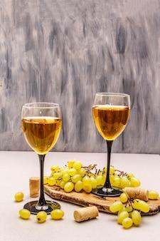 Copos de vinho, uvas frescas e rolhas na tábua de madeira