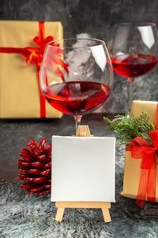 Copos de vista frontal de tela branca de presentes de natal de vinho em cavalete de madeira no escuro