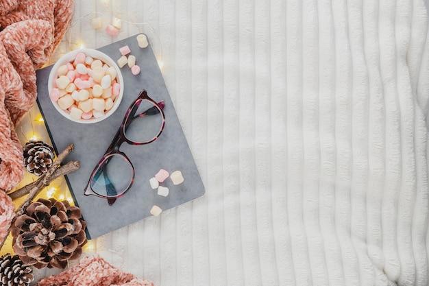 Copos de vista superior e agenda com chocolate quente no cobertor