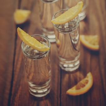 Copos de vodka com limão em fundo de madeira. imagem de tonalidade.