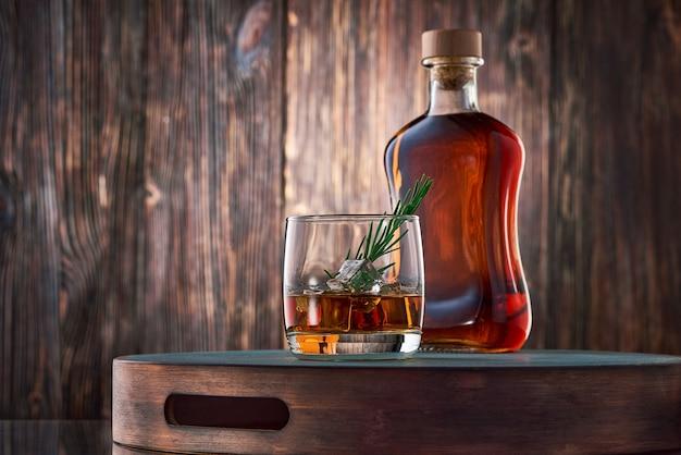 Copos de whisky e uma garrafa na mesa de madeira