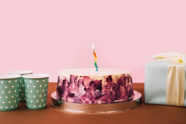 Copos descartáveis; caixa de presente e saboroso bolo na mesa contra o pano de fundo rosa