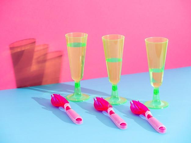 Copos descartáveis com água e talheres isolados no fundo meio azul e rosa, conceito de reciclagem