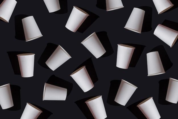 Copos descartáveis de papel branco de padrão abstrato em fundo preto, mock up