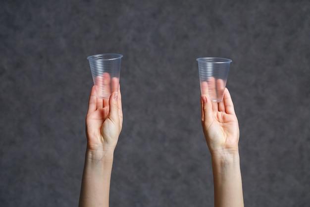 Copos descartáveis vazios plásticos transparentes de close-up em mãos femininas