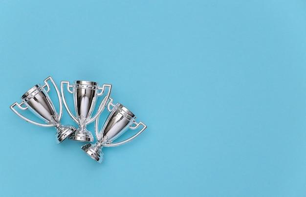 Copos do campeonato de esportes mini prata sobre um fundo azul pastel. copie o espaço. minimalismo esportivo. vista do topo
