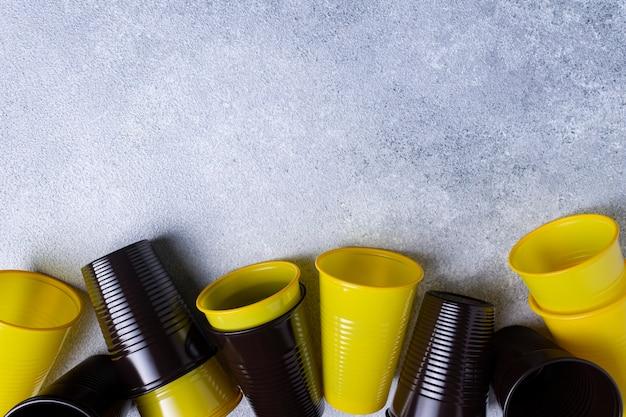 Copos e colheres de plástico estão espalhados pelo fundo cinza