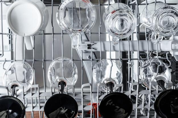 Copos e copos na máquina de lavar louça estão prontos para lavar