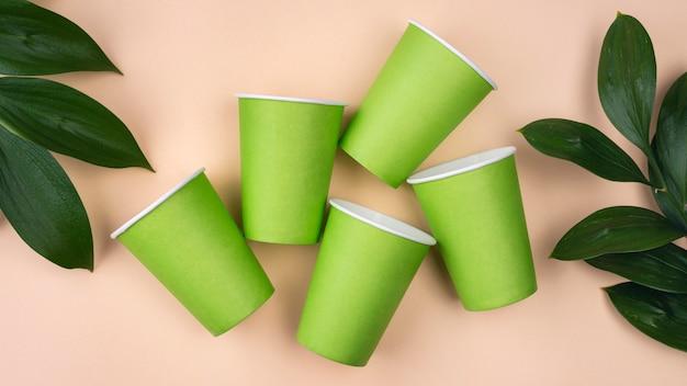 Copos e folhas verdes de talheres descartáveis ecológicos
