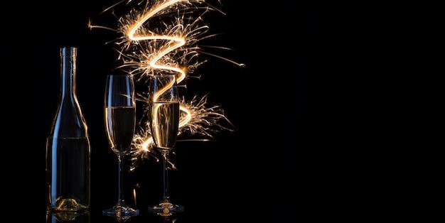 Copos e garrafa de champanhe nas faíscas festivas de bengala