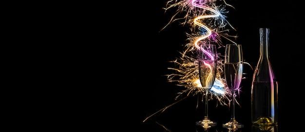 Copos e garrafa de champanhe no brilho das luzes coloridas de bengala