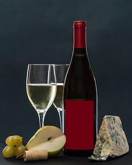 Copos e garrafa de vinho tinto com queijo de mofo azul e frutas