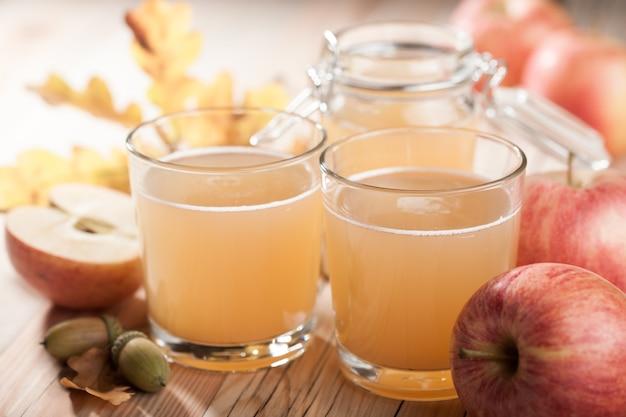 Copos e jarras de vidro de suco de maçã, maçãs, folhas caem na mesa de madeira