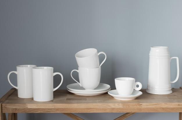 Copos e jarros brancos na prateleira de madeira em fundo cinza