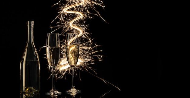 Copos e uma garrafa de champanhe nas luzes brilhantes de bengala