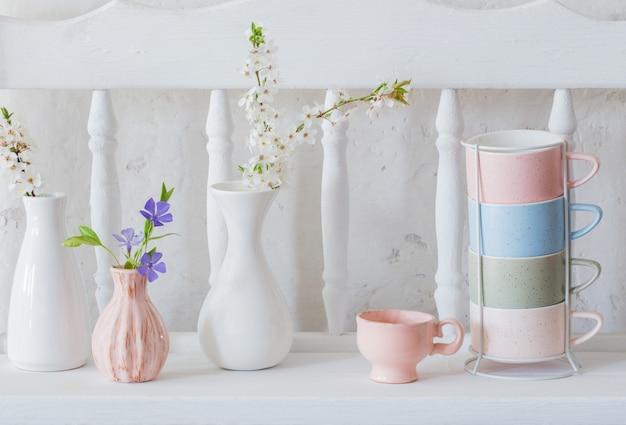 Copos e vasos com flores da primavera na prateleira branca de madeira vintage