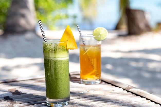 Copos frescos de cocktail verde e amarelo na praia
