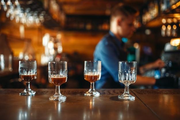 Copos no balcão do bar, barman