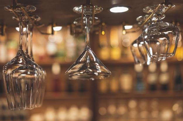 Copos para bebidas alcoólicas estão suspensos acima do bar.