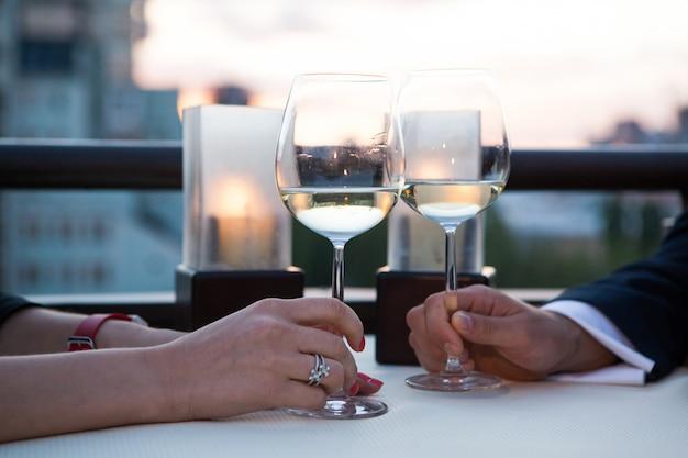 Copos tilintando com vinho branco e torradas.