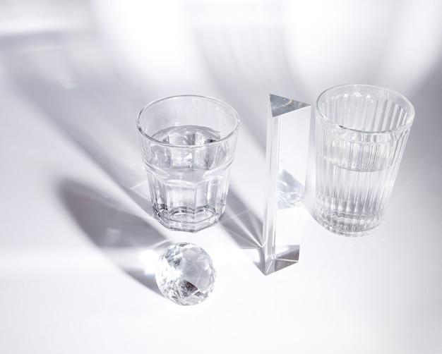 Copos transparentes de água; diamante e prisma em fundo branco com sombra