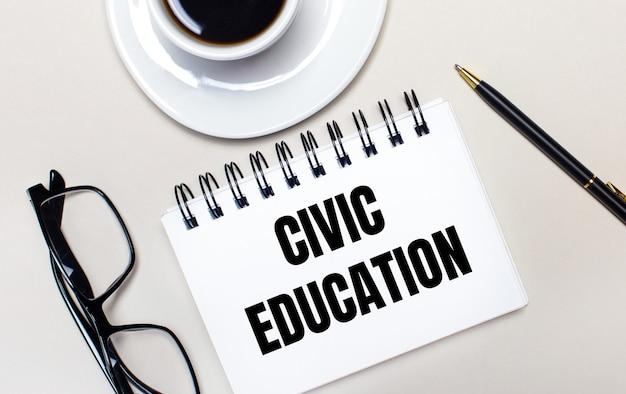 Copos, uma xícara de café branca, um caderno branco com as palavras educação cívica e uma caneta esferográfica repousam sobre uma superfície clara