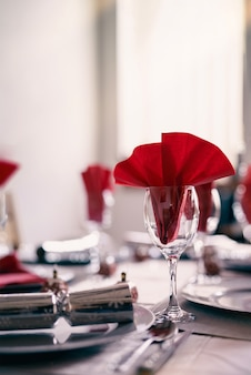 Copos vazios com guardanapo vermelho na mesa de jantar com uma luz brilhante brilhando pela janela.