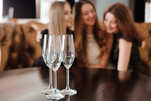 Copos vazios de champanhe no fundo das meninas.