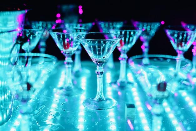 Copos vazios de cocktail com iluminação de cor ultravioleta