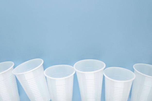Copos vazios de plástico brancos dispostos em uma fileira. conceito de problema ecológico.