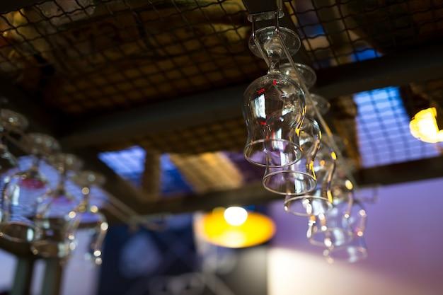 Copos vazios de vinho ou coquetel estão pendurados no bar em um bar ou pub