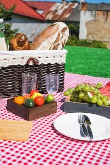 Copos vazios; talheres; frutas e legumes com cesta de piquenique no cobertor