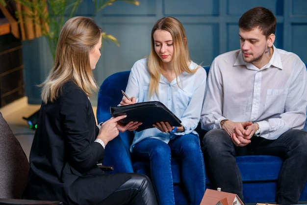 Cópula de jovens clientes, assinando contrato para a compra de casa nova, plana.