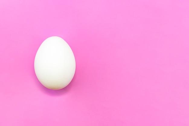Copyspace branco ovo de galinha em um fundo lilás rosa