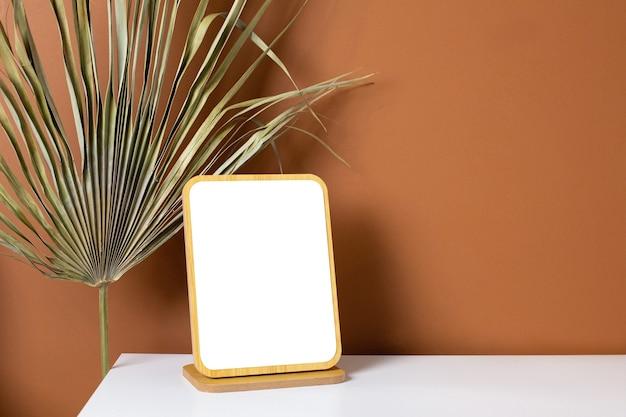 Copyspace e planta de moldura de madeira na mesa branca com fundo laranja escuro na parede