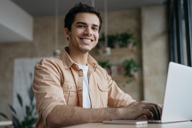 Copywriter freelancer sorridente usando laptop, trabalhando em casa