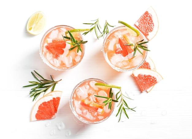 Coquetéis alcoólicos paloma com tequila e gelo guarnecidos com fatias de limão e grapefruit