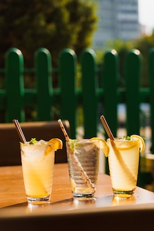 Coquetéis com limão e menta em copos com tubo em uma mesa de madeira no contexto de um restaurante