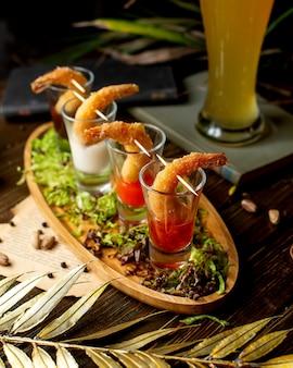 Coquetéis de camarão servidos com alface e copo de cerveja